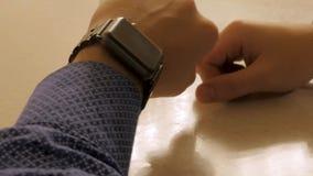Όμορφος μοντέρνος αρσενικός χρόνος διαχείρισης στο ηλεκτρονικό ρολόι Νεαρός άνδρας που ελέγχει το σύγχρονο ρολόι καρπών Στοκ Εικόνες