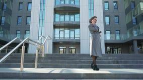 Όμορφος, μοντέρνος, επιχειρησιακή γυναίκα που μιλά στο τηλεφωνικό υπαίθριο κοντινό κτίριο γραφείων Είναι πολύ μια ευτυχής, εύθυμη απόθεμα βίντεο