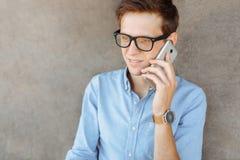 Όμορφος μοντέρνος επιχειρησιακός τύπος με τα γυαλιά, που θέτουν στην παραλία, hipster μιλώντας στο τηλέφωνο, εργασία στις διακοπέ στοκ εικόνα με δικαίωμα ελεύθερης χρήσης