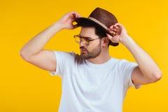 όμορφος μοντέρνος νεαρός άνδρας στο καπέλο και γυαλιά ηλίου που κοιτάζουν μακριά Στοκ Φωτογραφίες