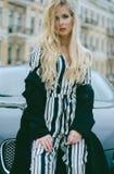 Όμορφος μοντέρνος ξανθός με μακρυμάλλη σε ένα μαύρο παλτό και ριγωτές φόρμες που θέτουν τη συνεδρίαση σε ένα μαύρο αυτοκίνητο στη Στοκ Φωτογραφίες
