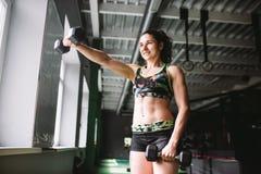 Όμορφος μοντέρνος Το νέο κορίτσι που κάνει τις ασκήσεις με τους αλτήρες για τους μυς παραδίδει τη γυμναστική στοκ εικόνες