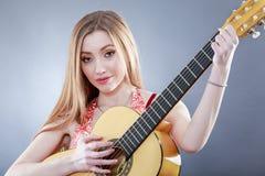 Όμορφος νέος ένας ξανθός με μια κλασσική κιθάρα στοκ εικόνα