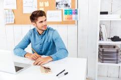 Όμορφος νέος έξυπνος επιχειρηματίας που εργάζεται με τα έγγραφα και τον υπολογιστή Στοκ Φωτογραφία