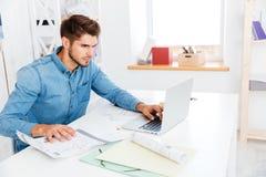 Όμορφος νέος έξυπνος επιχειρηματίας που εργάζεται με τα έγγραφα και τον υπολογιστή Στοκ Εικόνες