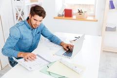 Όμορφος νέος έξυπνος επιχειρηματίας που εργάζεται με τα έγγραφα και τον υπολογιστή Στοκ φωτογραφίες με δικαίωμα ελεύθερης χρήσης