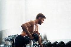 Όμορφος νέος αθλητής που επιλύει στη γυμναστική Στοκ Φωτογραφία