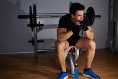 όμορφος νέος αθλητής που στηρίζεται μετά από benching στοκ φωτογραφίες
