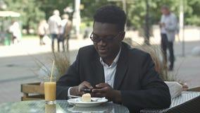 Όμορφος νέος αμερικανικός επιχειρηματίας afro που χρησιμοποιεί το έξυπνο τηλέφωνο, μήνυμα η φίλη του, που τρώει στον καφέ απόθεμα βίντεο