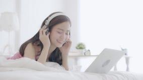 Όμορφος νέος ανεξάρτητος ασιατικός λειτουργώντας φορητός προσωπικός υπολογιστής χαμόγελου γυναικών και ομιλών πελάτης με το τηλέφ απόθεμα βίντεο