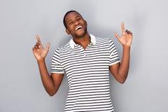Όμορφος νέος αφρικανικός τύπος που δείχνει προς τα πάνω στο γκρίζο κλίμα Στοκ εικόνα με δικαίωμα ελεύθερης χρήσης