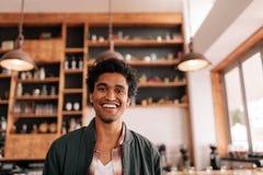 Όμορφος νέος αφρικανικός τύπος που στέκεται σε μια καφετερία και ένα χαμόγελο Στοκ Φωτογραφία