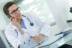 Όμορφος νέος γιατρός που μιλά στο τηλέφωνο στο γραφείο Στοκ Εικόνα