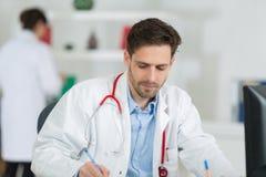 Όμορφος νέος γιατρός στην εργασία στην αρχή Στοκ Εικόνες