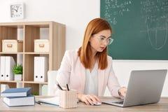 Όμορφος νέος δάσκαλος με τη συνεδρίαση lap-top στον πίνακα Στοκ Εικόνες