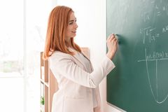 Όμορφος νέος δάσκαλος που γράφει στον πίνακα Στοκ Φωτογραφίες