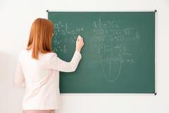 Όμορφος νέος δάσκαλος που γράφει στον πίνακα Στοκ Εικόνες
