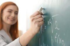Όμορφος νέος δάσκαλος που γράφει στον πίνακα Στοκ Φωτογραφία