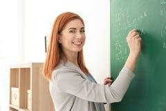 Όμορφος νέος δάσκαλος που γράφει στον πίνακα Στοκ Εικόνα