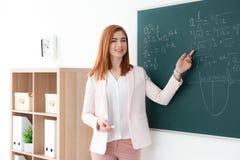 Όμορφος νέος δάσκαλος που εξηγεί math τους τύπους γραπτούς Στοκ εικόνες με δικαίωμα ελεύθερης χρήσης