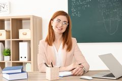 Όμορφος νέος δάσκαλος που εργάζεται στον πίνακα Στοκ Εικόνες