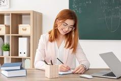 Όμορφος νέος δάσκαλος που εργάζεται στον πίνακα Στοκ Φωτογραφίες