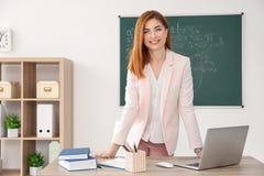 Όμορφος νέος δάσκαλος που στέκεται κοντά στον πίνακα Στοκ Εικόνες