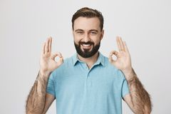 Όμορφος νέος ενήλικος με τη γενειάδα και λαμπρό χαμόγελο, που παρουσιάζουν την εντάξει χειρονομία ή approvement με δύο χέρια, πέρ Στοκ φωτογραφίες με δικαίωμα ελεύθερης χρήσης