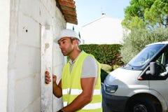 Όμορφος νέος επιστάτης που εποπτεύει μια περιοχή contruction ανακαίνισης σπιτιών Στοκ Εικόνες