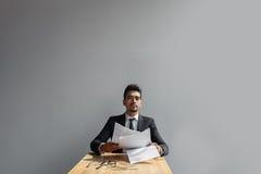 Όμορφος νέος επιχειρηματίας με τα έγγραφα που απομονώνεται υπό εξέταση πέρα από το γκρίζο υπόβαθρο Στοκ Φωτογραφία