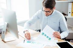 Όμορφος νέος επιχειρηματίας που λειτουργούν με τα έγγραφα και υπολογιστής στην αρχή Στοκ Εικόνες