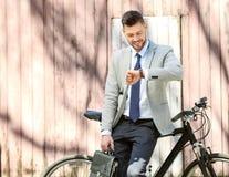 Όμορφος νέος επιχειρηματίας που εξετάζει το ρολόι στεμένος κοντά στο ποδήλατο υπαίθρια στοκ φωτογραφίες με δικαίωμα ελεύθερης χρήσης