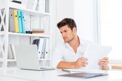 Όμορφος νέος επιχειρηματίας που εργάζεται με τα έγγραφα και το lap-top Στοκ Εικόνες