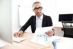 Όμορφος νέος επιχειρηματίας που εργάζεται με τα έγγραφα στην αρχή Στοκ φωτογραφία με δικαίωμα ελεύθερης χρήσης