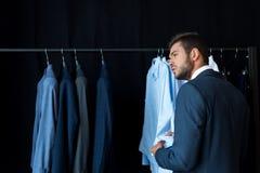 όμορφος νέος επιχειρηματίας που κοιτάζει μακριά επιλέγοντας το κοστούμι Στοκ Φωτογραφία
