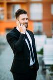 Όμορφος νέος επιχειρηματίας που περπατά στην οδό και που μιλά στο τηλέφωνό του Στοκ Φωτογραφίες