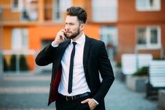 Όμορφος νέος επιχειρηματίας που περπατά στην οδό και που μιλά στο τηλέφωνό του Στοκ φωτογραφίες με δικαίωμα ελεύθερης χρήσης