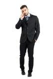 Όμορφος νέος επιχειρηματίας στο τηλέφωνο που κοιτάζει και που περπατά προς τη κάμερα Στοκ Εικόνες