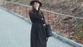 Όμορφος νέος ευτυχής περίπατος γυναικών κάτω στο πάρκο, μακρυμάλλης, παλτό φθινοπώρου, πορφυρό καπέλο, αργός πυροβολισμός MO sted απόθεμα βίντεο