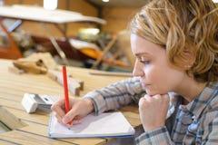 Όμορφος νέος θηλυκός ξυλουργός που παίρνει τις σημειώσεις στο εργαστήριο Στοκ εικόνες με δικαίωμα ελεύθερης χρήσης