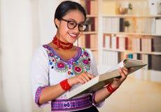 Όμορφος νέος δικηγόρος που φορά την παραδοσιακά των Άνδεων μπλούζα και τα γυαλιά, που κρατούν την ανάγνωση βιβλίων, υπόβαθρο ραφι Στοκ Εικόνες