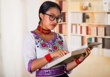 Όμορφος νέος δικηγόρος που φορά την παραδοσιακά των Άνδεων μπλούζα και τα γυαλιά, που κρατούν την ανάγνωση βιβλίων, υπόβαθρο ραφι Στοκ φωτογραφία με δικαίωμα ελεύθερης χρήσης