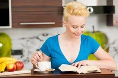 Όμορφος νέος καυκάσιος ξανθός καφές κατανάλωσης γυναικών στο ki Στοκ Φωτογραφίες