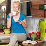 Όμορφος νέος καυκάσιος ξανθός καφές κατανάλωσης γυναικών στο ki Στοκ φωτογραφία με δικαίωμα ελεύθερης χρήσης