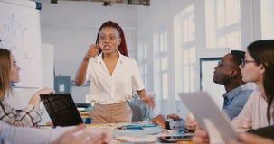 Όμορφος νέος μαύρος ηγέτης επιχειρησιακών γυναικών που μιλά στους multiethnic υπαλλήλους στο οικονομικό σεμινάριο εμπειρογνωμόνων απόθεμα βίντεο