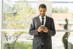 Όμορφος νέος μαύρος με το κινητό τηλέφωνο Στοκ Εικόνες