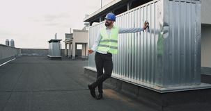 Όμορφος νέος μηχανικός ή αρχιτέκτονας με ένα κράνος ασφάλειας στη στέγη του εργοτάξιου οικοδομής που απολαμβάνει το σπάσιμο απόθεμα βίντεο