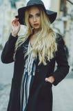 Όμορφος νέος μοντέρνος ένας ξανθός με μακρυμάλλη στους περίπατους μαύρων παλτών και μαύρων καπέλων μέσω της πόλης Φθινόπωρο Μόδα  Στοκ φωτογραφία με δικαίωμα ελεύθερης χρήσης