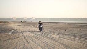 Όμορφος νέος μοτοσυκλετιστής γυναικών με τη φίλη του που οδηγά μια μοτοσικλέτα σε μια έρημο στο ηλιοβασίλεμα ή την ανατολή χορεύο φιλμ μικρού μήκους