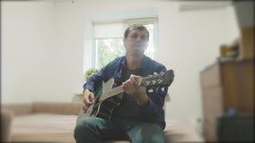 Όμορφος νέος μουσικός που παίζει την κιθάρα και το τραγούδι Άτομο που παίζει το ακουστικό σε αργή κίνηση βίντεο κιθάρων κοντά επά φιλμ μικρού μήκους
